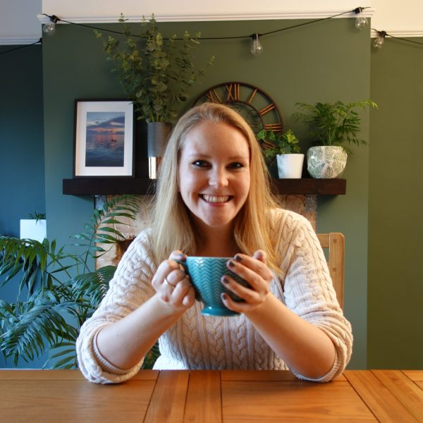 female lifecoach drinking coffee in green home office