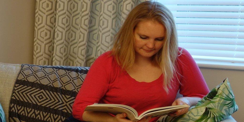 Julia Davies, aka The Simplicity Strategist, reads a book in her botanic geometric living room